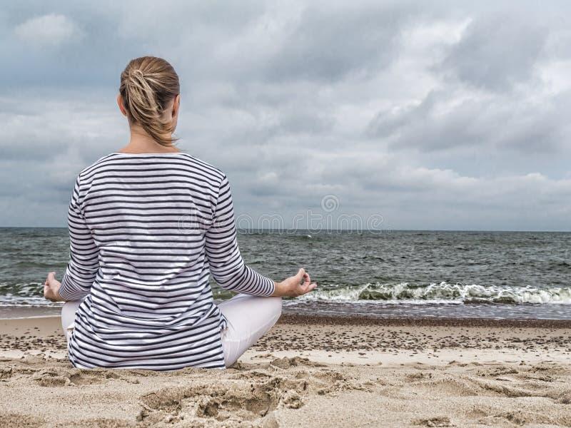 El Meditating en la playa imagenes de archivo