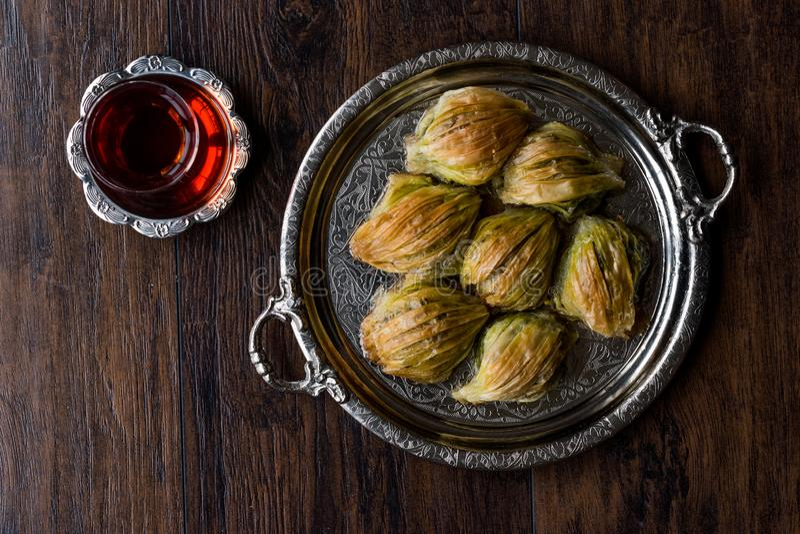 El mejillón turco del Baklava de Midye forma Baklawa con el polvo verde del pistacho, la crema de la mantequilla y el té tradicio foto de archivo libre de regalías