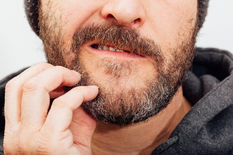 El mejor hombre del ager que rasguña la barba imagen de archivo