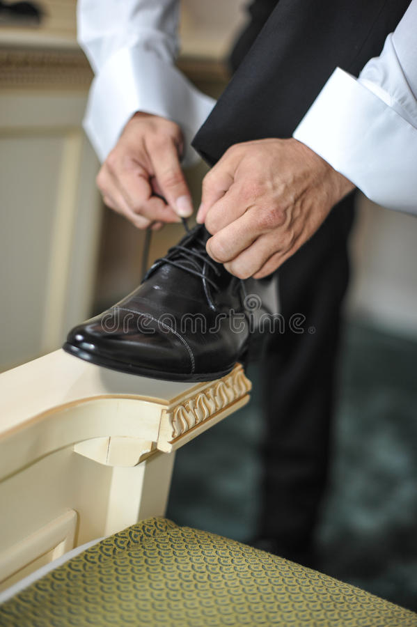 El mejor hombre que consigue listo por un día especial Un novio que pone en los zapatos como él consigue vestido en desgaste form fotos de archivo libres de regalías