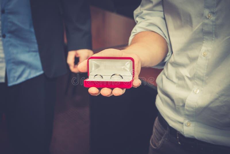 El mejor hombre que lleva a cabo los anillos de bodas imagen de archivo libre de regalías