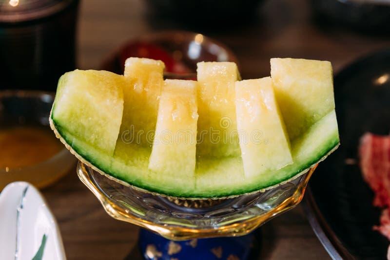 El melón de ligamaza japonés se corta a través hasta el final con la cáscara Dulce y blando para el aperitivo foto de archivo