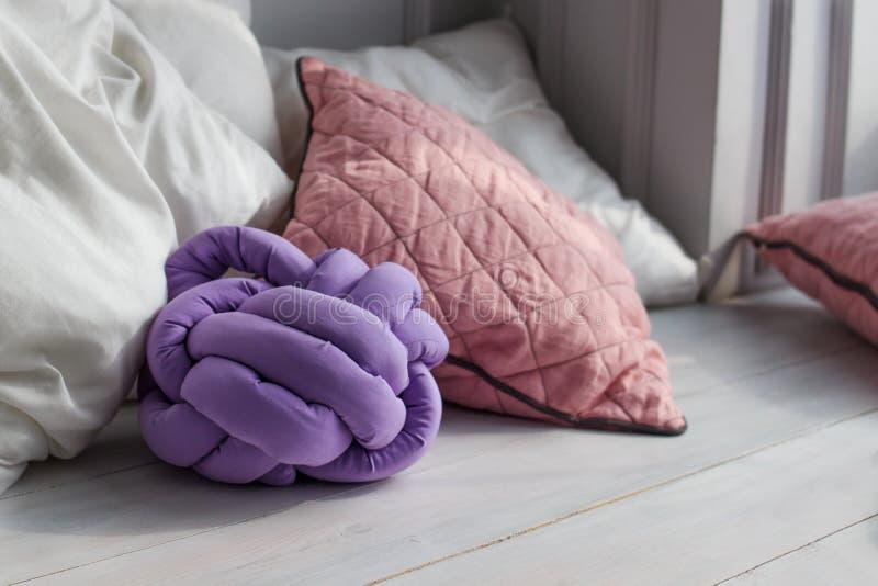 El melocotón lindo coloreó la almohada del nudo en dentro el fondo El nudo original del amortiguador, materias textiles del puño foto de archivo libre de regalías