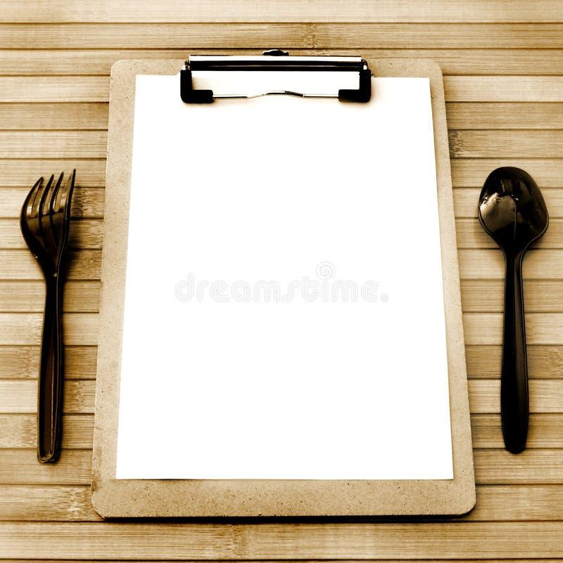 El menú de papel con la bifurcación plástica negra y la cuchara yuxtaponen en una tabla de madera tienen espacio, estilo del vint foto de archivo