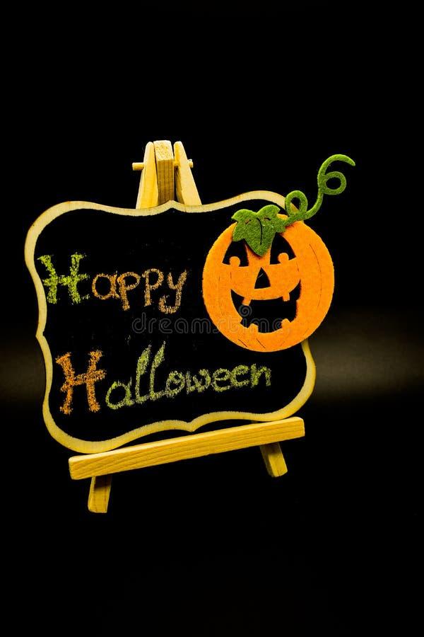 El mensaje del feliz Halloween escribe en una pizarra con una calabaza Aislado en fondo negro fotos de archivo libres de regalías