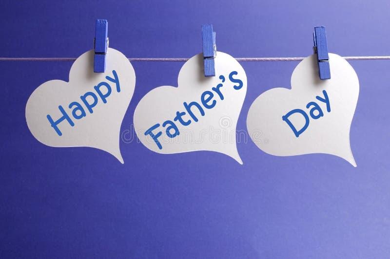 El mensaje feliz del día de padres escrito en la forma blanca del corazón marca el colgante con etiqueta de clavijas azules en una foto de archivo libre de regalías
