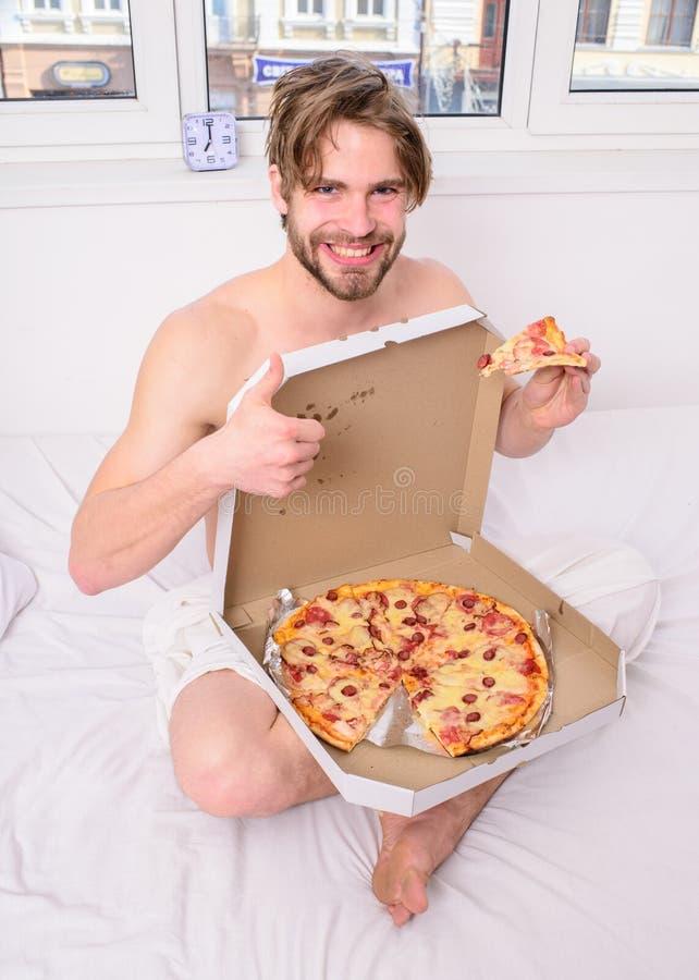 El mensajero atractivo entrega la satisfacción gastronómica Satisfacción gastronómica Hermosos barbudos del hombre comen la pizza imagen de archivo libre de regalías
