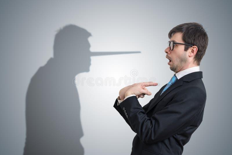 El mentiroso tiene sombra con la nariz larga Concepto de la conciencia foto de archivo