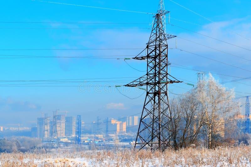 El metal apoya de la línea eléctrica de alto voltaje en frente, contra el fondo, en una neblina escarchada, los edificios altos r fotos de archivo libres de regalías