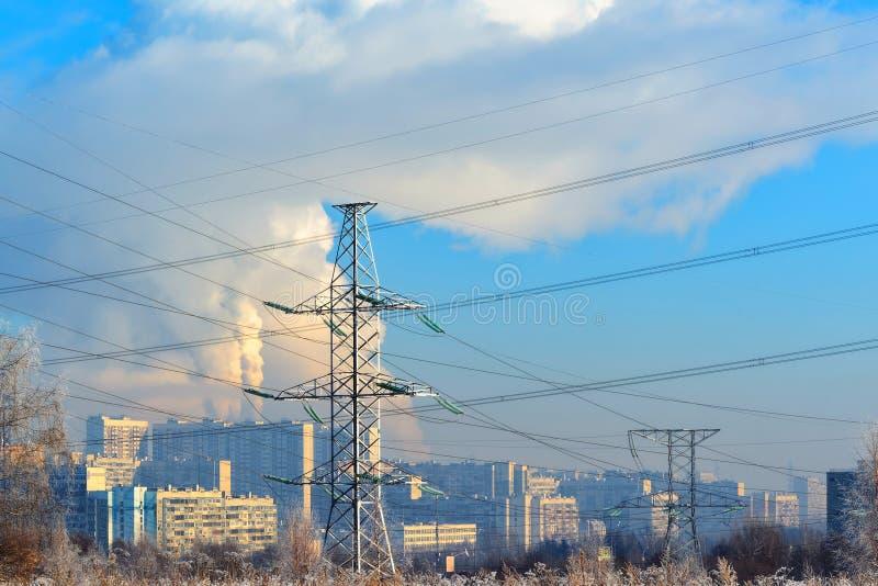 El metal apoya de la línea eléctrica de alto voltaje en frente, contra el fondo, en una neblina escarchada, los edificios altos r imagenes de archivo