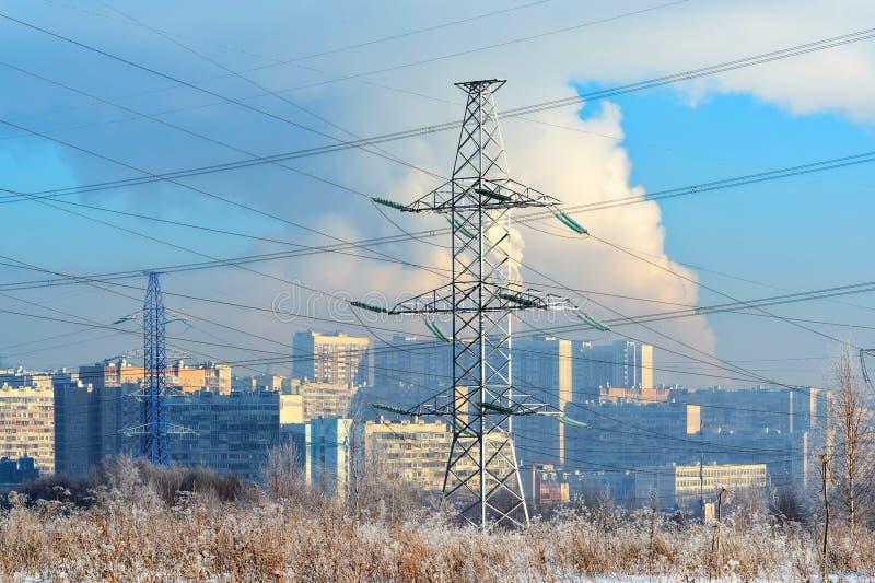 El metal apoya de la línea eléctrica de alto voltaje en frente, contra el fondo, en una neblina escarchada, los edificios altos r fotos de archivo