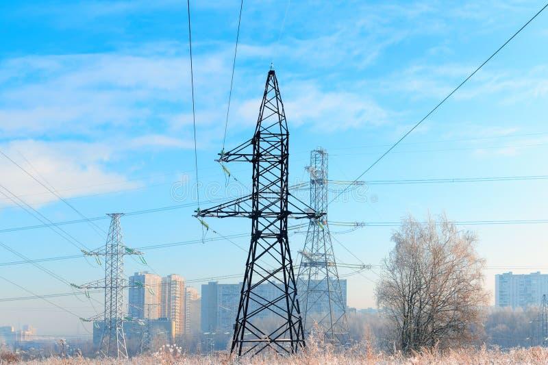 El metal apoya de la línea eléctrica de alto voltaje en frente, contra el fondo, en una neblina escarchada, los edificios altos r imagen de archivo