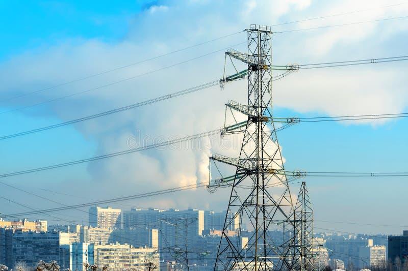El metal apoya de la línea eléctrica de alto voltaje en frente, contra el fondo, en una neblina escarchada, los edificios altos r fotografía de archivo libre de regalías