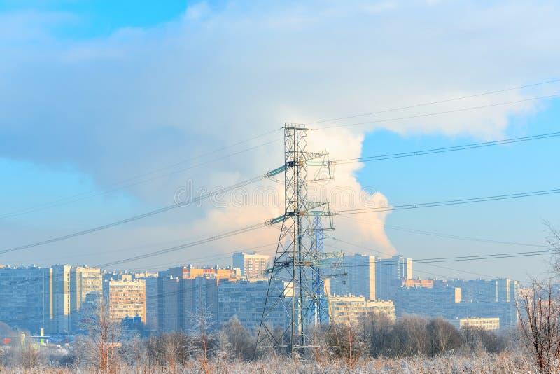 El metal apoya de la línea eléctrica de alto voltaje en frente, contra el fondo, en una neblina escarchada, los edificios altos r imagen de archivo libre de regalías