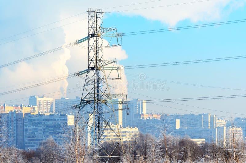 El metal apoya de la línea eléctrica de alto voltaje en frente, contra el fondo, en una neblina escarchada, los edificios altos r fotografía de archivo
