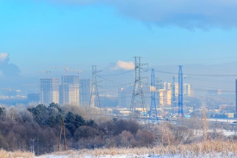 El metal apoya de la línea eléctrica de alto voltaje en frente, contra el fondo, en una neblina escarchada, los edificios altos r foto de archivo