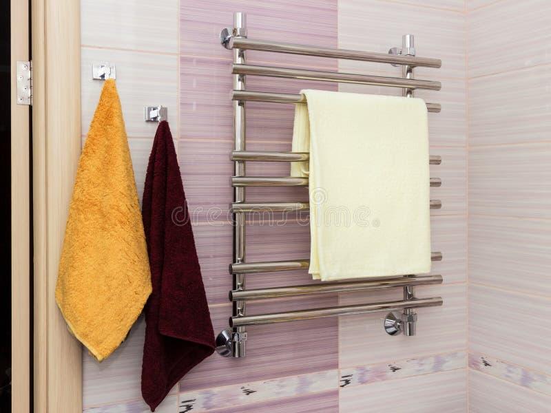 El metal brillante calentó el carril de toalla fijado en la toalla seca del cuarto de baño fotografía de archivo