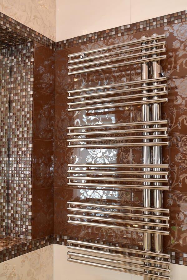 El metal calentó el carril de toalla en una pared en un cuarto de baño fotos de archivo libres de regalías
