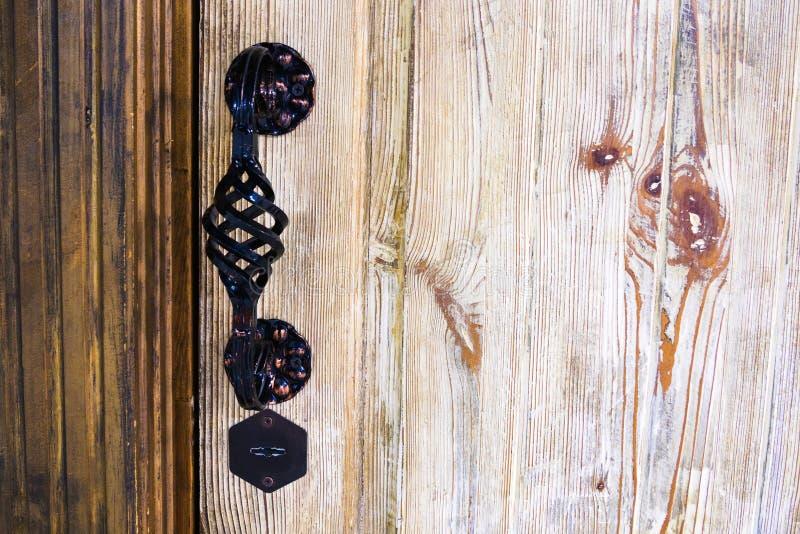 El metal del viejo estilo talló el tirador de puerta y la cerradura en el fondo de madera beige, espacio de la copia foto de archivo libre de regalías