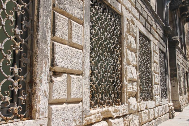 El metal ralla en las ventanas de las casas viejas en Venecia, fotografía de archivo libre de regalías