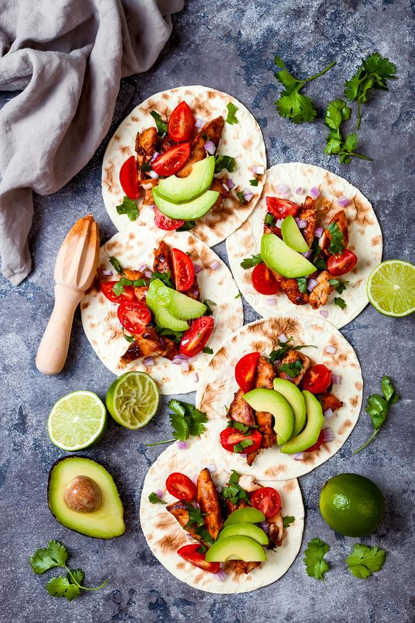 El mexicano asó a la parrilla los tacos de pollo con el aguacate, tomate, cebolla en la tabla de piedra rústica Receta para el pa imagen de archivo libre de regalías
