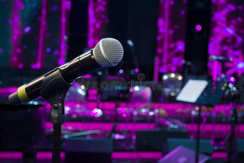 El micrófono contra y las notas de la música empañan el backgroun ligero colorido imagen de archivo