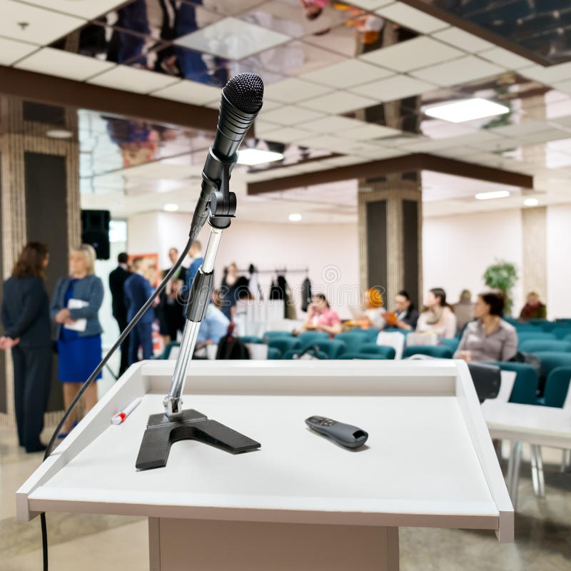 El micrófono en el podio del discurso sobre el extracto empañó la foto del fondo de la sala de conferencias o de la sala de semin fotografía de archivo libre de regalías