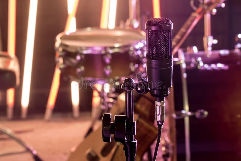 El micrófono en un estudio de grabación o un cierre de la sala de conciertos para arriba de la batería y una guitarra acústica en fotografía de archivo libre de regalías