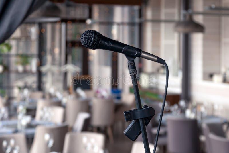 El micr?fono del hierro del negro del primer se coloca en el fondo de etapa del pasillo del restaurante servido para el banquete  imagen de archivo libre de regalías