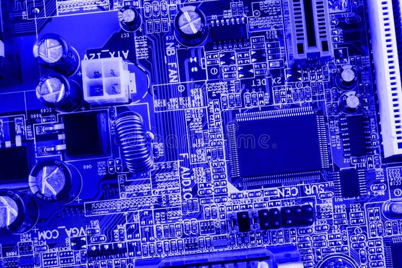 El microchip, filtro, condensadores, batería, conectores en la placa madre de un fondo azul del ordenador moderno cierra macro fotos de archivo libres de regalías