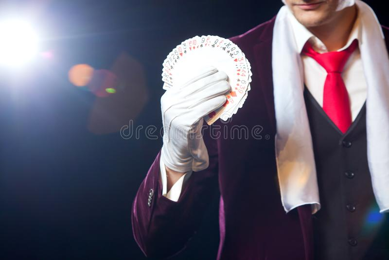 El Midsection de la demostración del mago avivó hacia fuera tarjetas contra fondo negro Mago, hombre del juglar, persona divertid foto de archivo