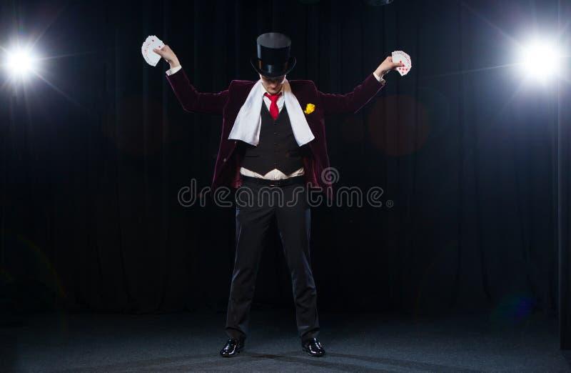 El Midsection de la demostración del mago avivó hacia fuera tarjetas contra fondo negro Mago, hombre del juglar, persona divertid fotos de archivo libres de regalías