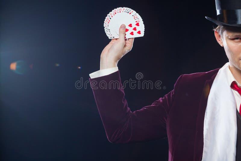 El Midsection de la demostración del mago avivó hacia fuera tarjetas contra fondo negro Mago, hombre del juglar, persona divertid imagen de archivo