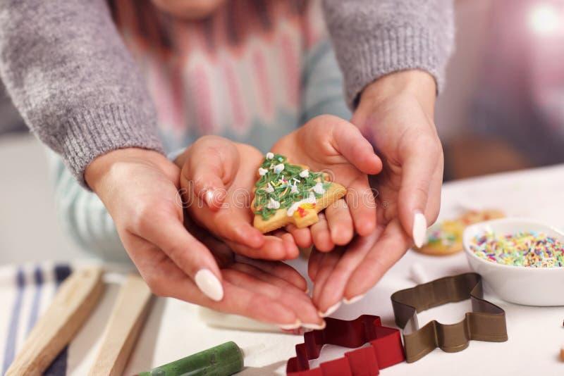El Midsection de la madre y de la hija da sostener las galletas de la Navidad foto de archivo
