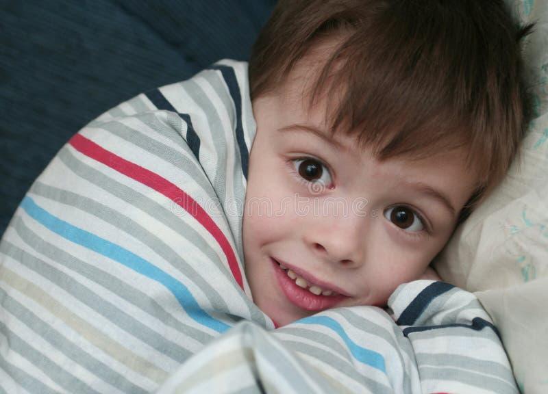 El miedo del muchacho que duerme en una cama foto de archivo