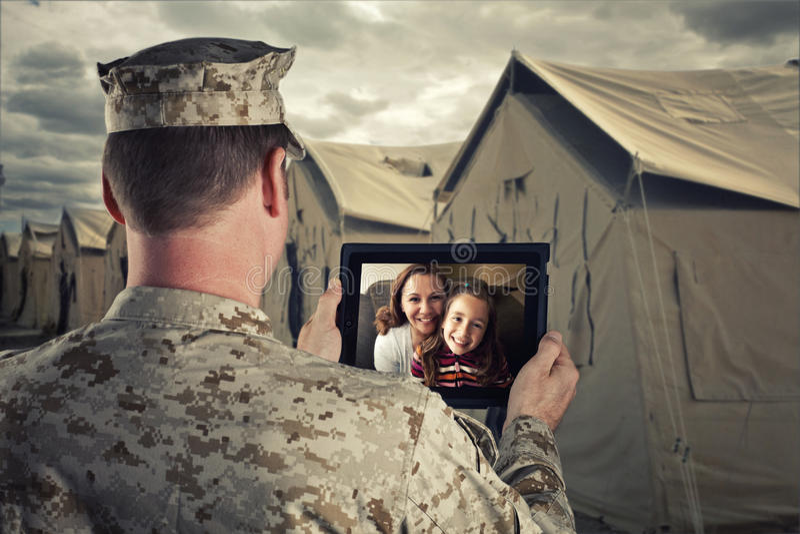 El militar desplegado charla con la familia foto de archivo