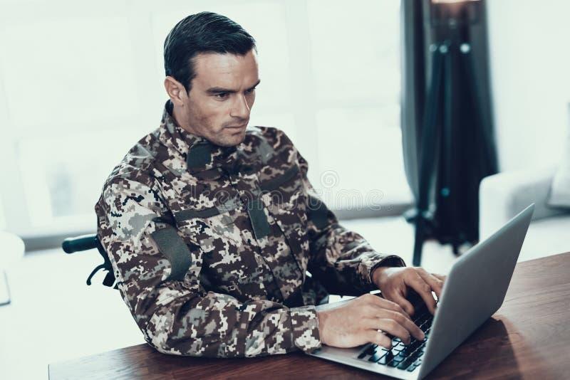 El militar serio utiliza el cuaderno en sala de estar fotografía de archivo