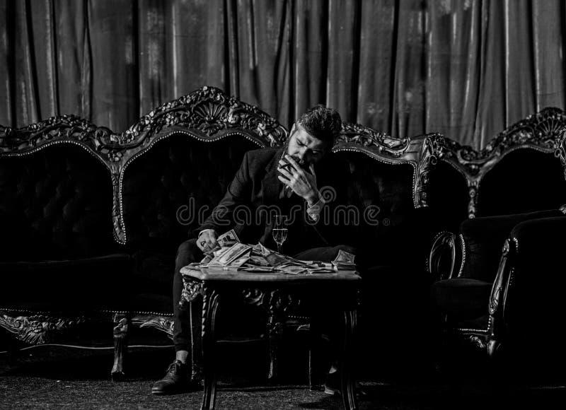 El millonario en traje elegante fuma y bebe en el sofá lujoso foto de archivo