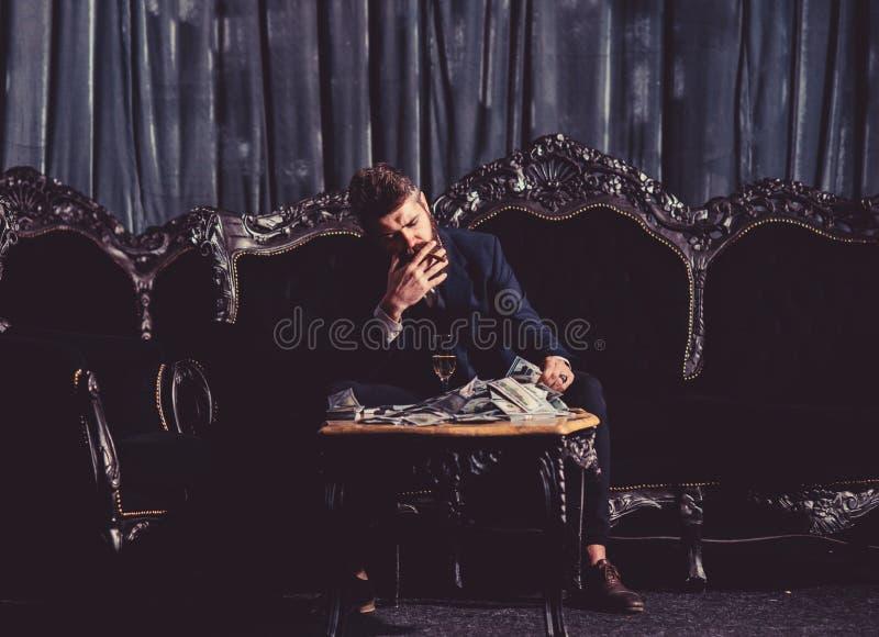 El millonario en traje elegante fuma y bebe en el sofá lujoso imagen de archivo libre de regalías