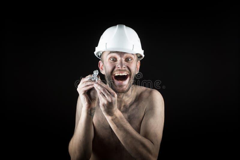 El minero feliz muestra una pepita de plata fotografía de archivo