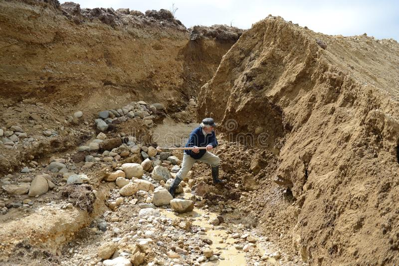El minero mina el oro al borde de la tierra foto de archivo