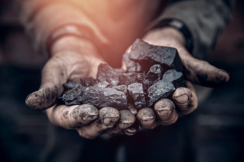 El minero sostiene el carbón, textura de la palma Concepto que mina, piedra negra fotografía de archivo