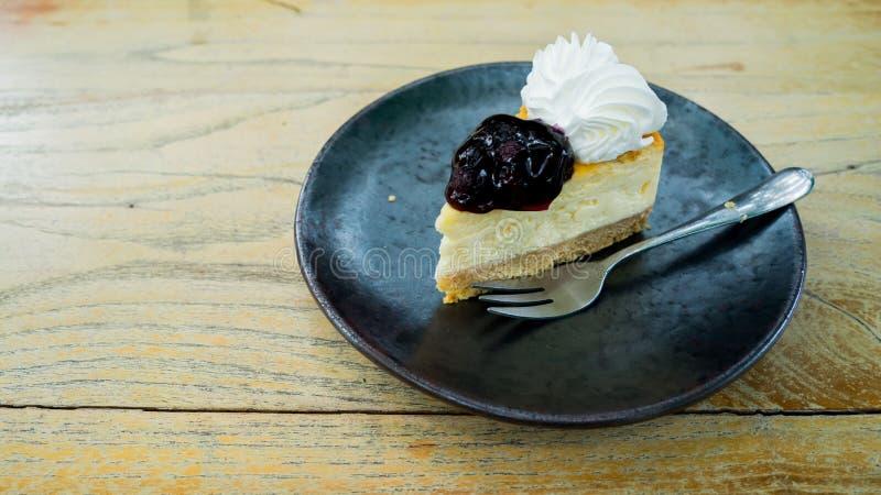 El mini pastel de queso del arándano se centró en placa negra con la bifurcación en la tabla de madera imágenes de archivo libres de regalías