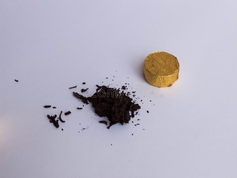El mini tuocha presionó té de la PU 'er de la provincia china Yunnan envolvió en hoja de oro en el fondo blanco foto de archivo