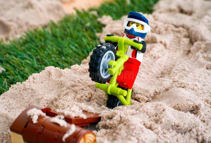El minifigure del ciclista de Lego en la bici de montaña hace algunos saltos del l imagen de archivo