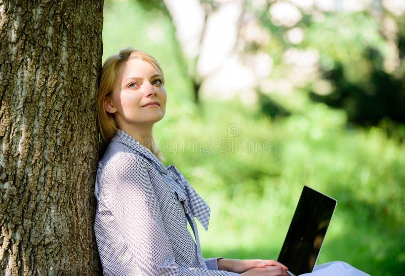 El minuto para se relaja Trabajo de la muchacha con el ordenador portátil en parque sentarse en hierba Tecnología de la educación fotos de archivo libres de regalías