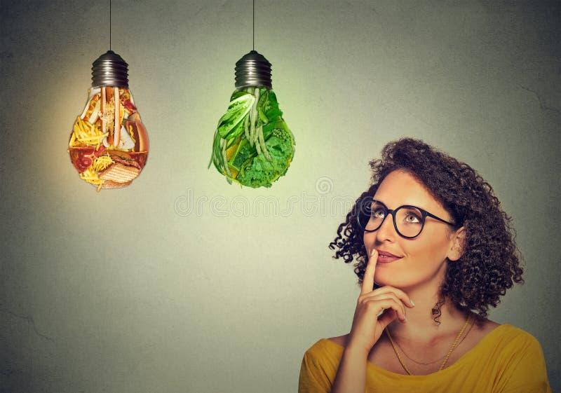 El mirar de pensamiento de la mujer para arriba la comida basura y las verduras verdes formadas como bombilla imágenes de archivo libres de regalías