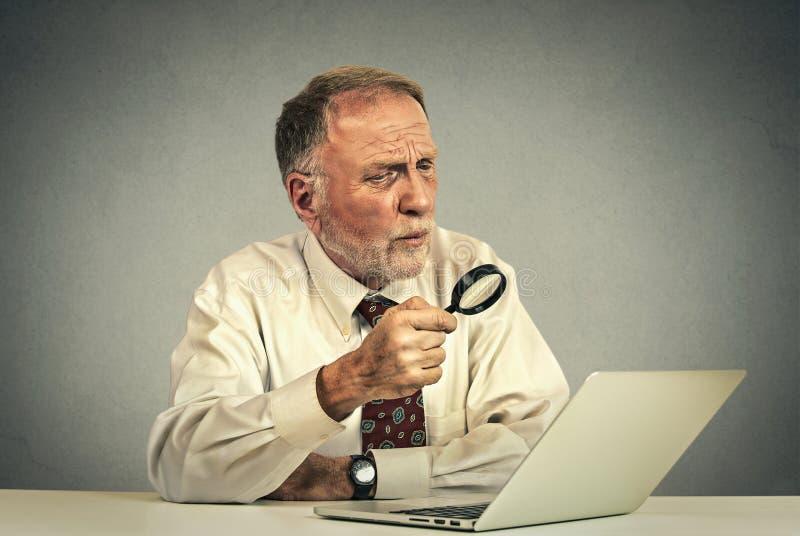 El mirar de trabajo del hombre mayor a través de la lupa la pantalla del ordenador portátil fotos de archivo libres de regalías