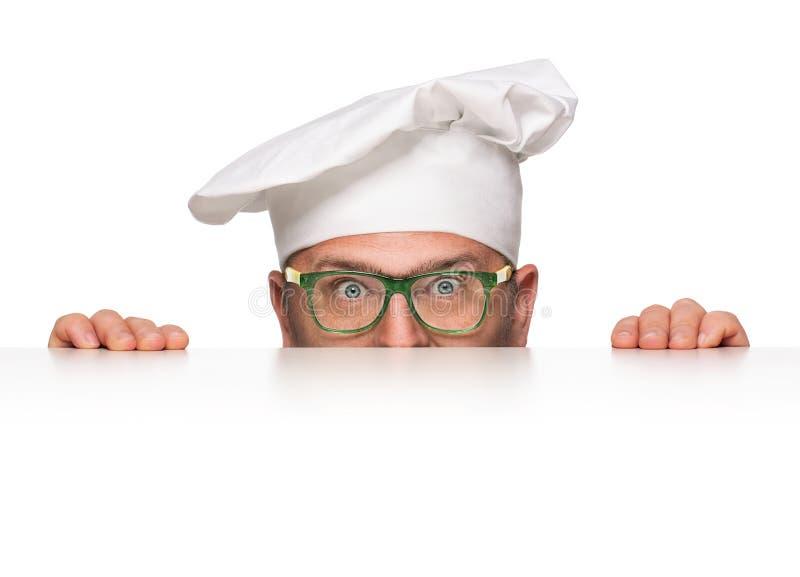 El mirar a escondidas divertido del cocinero fotografía de archivo
