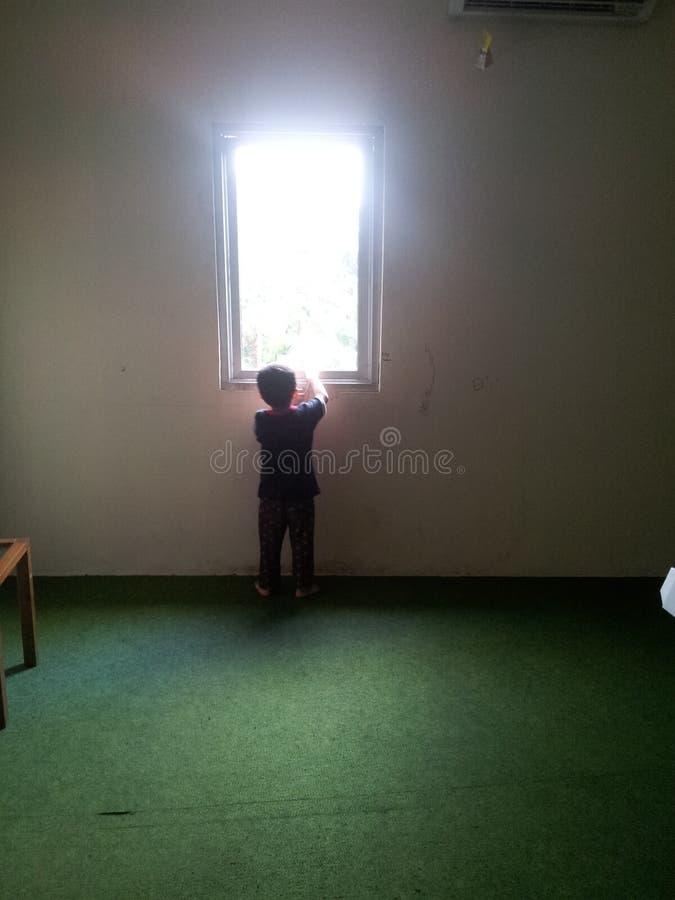 El mirar a escondidas a través de la ventana imagenes de archivo